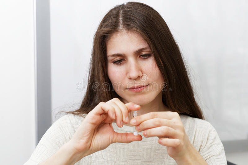 Young woman holding a sampler of perfume royalty free stock image