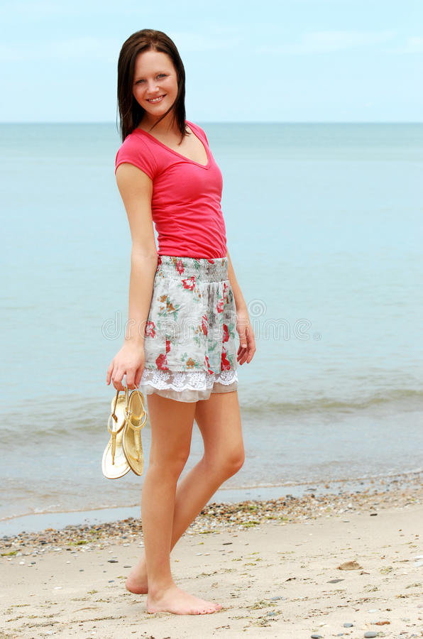 Young Woman Holding Sandals On The Beach Royalty Free Stock Image
