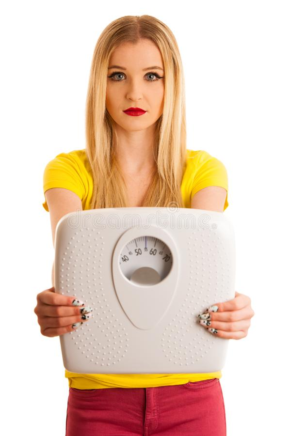 Young woman holding a scale as gesture for weight loose isolated royalty free stock photography