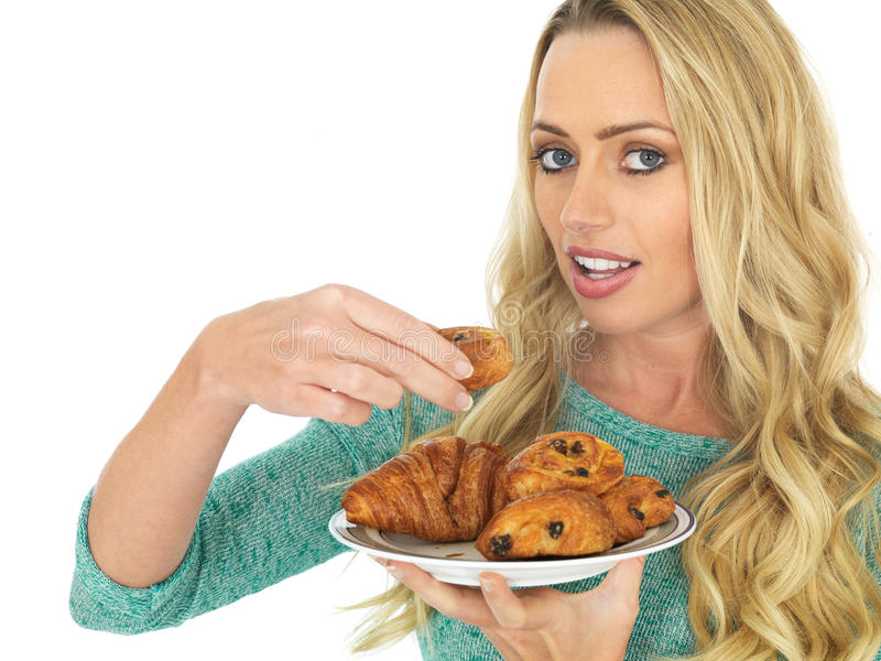 Young Woman Holding a Selection of Danish Pastries. A DSLR royalty free image, of attractive young healthy woman, with long blonde hair, eating from a selection stock photography