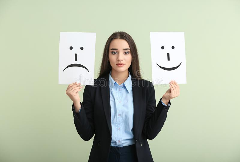 Young woman holding sheets of paper with drawn emoticons on light background royalty free stock image