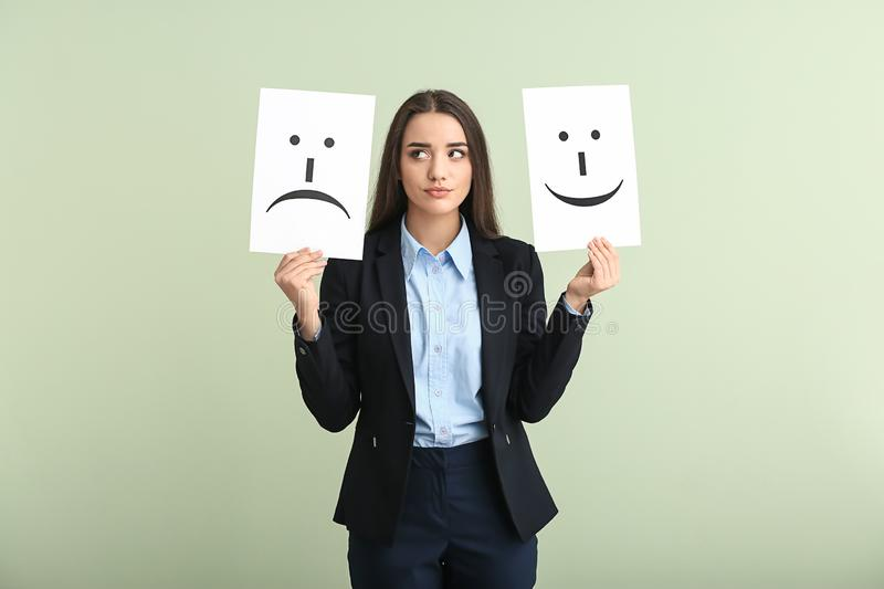 Young woman holding sheets of paper with drawn emoticons on light background stock photography