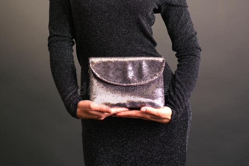 Young woman holding a shining clutch isolated on background stock photography