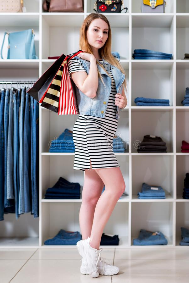 Young woman holding shopping bags and choosing ladies wear in clothing store.  stock photos