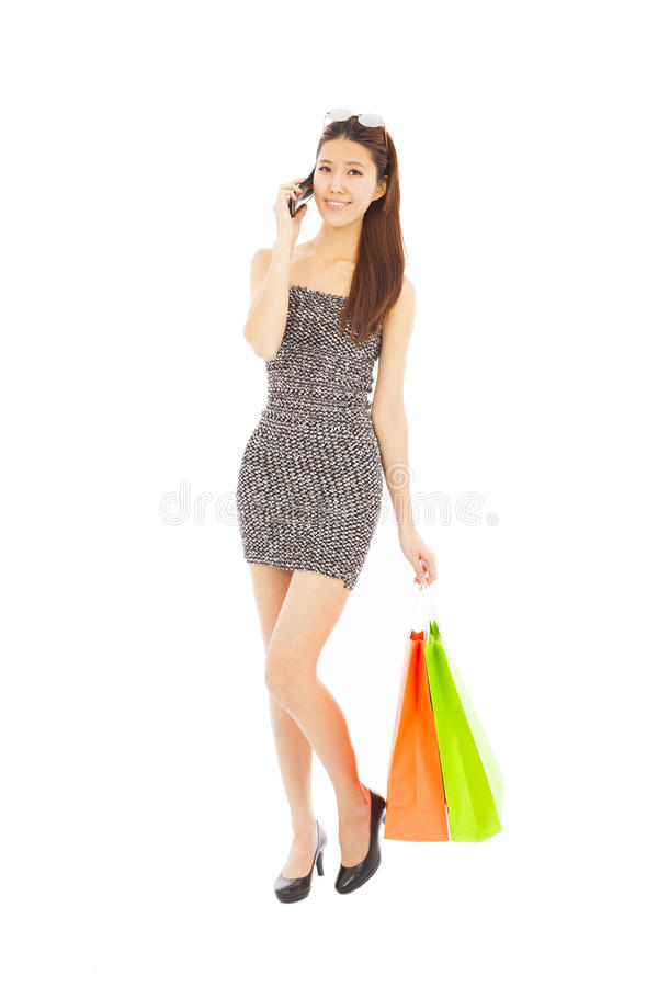 Young woman holding shopping bags and talking on the phone stock photo