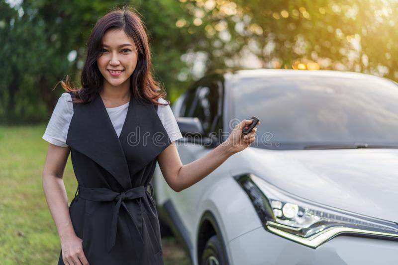 Woman holding smart key remote with a car stock photography