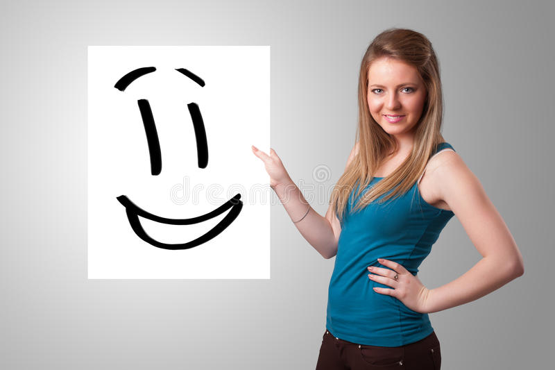Young woman holding smiley face drawing stock photos