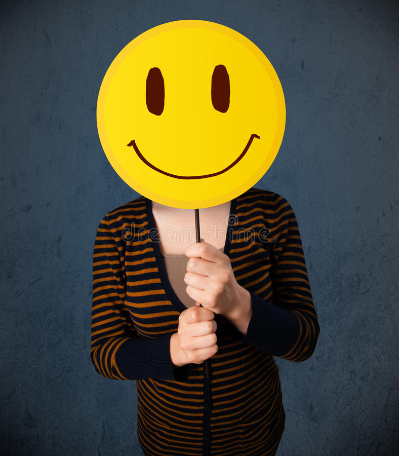 Young woman holding a smiley face emoticon. Young lady holding a yellow smiley face emoticon in front of her head stock photo