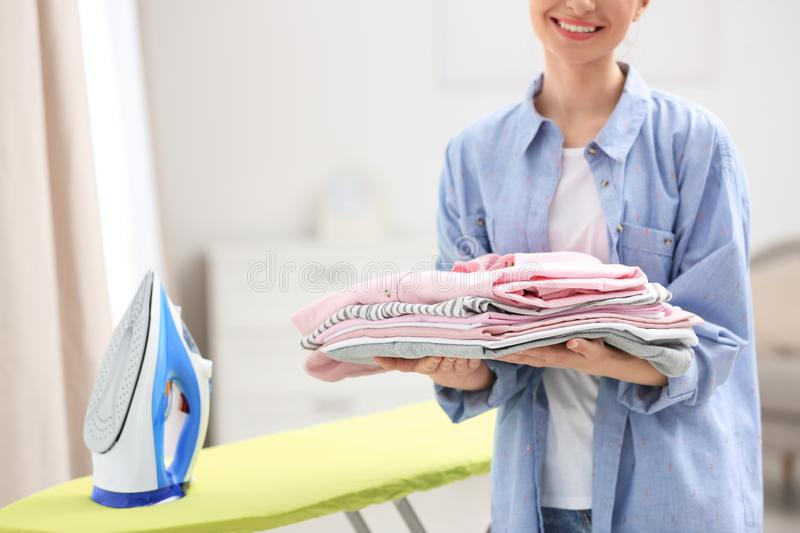 Young woman holding stack of clean laundry, closeup. Space for text. Young woman holding stack of clean laundry indoors, closeup. Space for text stock image