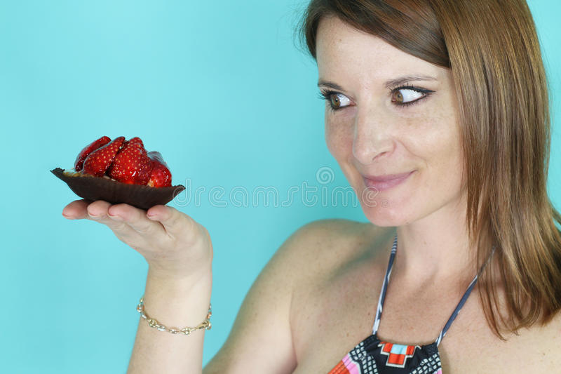 Young woman holding a strawberry tart. Over a blue background stock photo