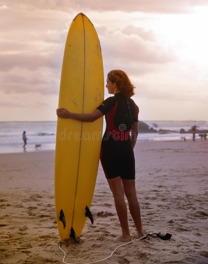 Young woman holding surfboard stock photography