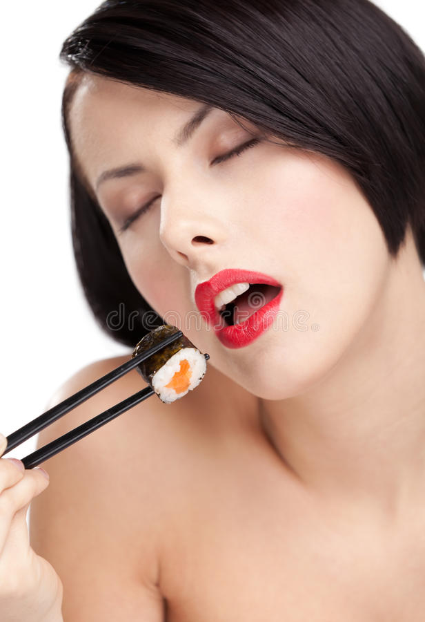 Young woman holding sushi, eyes closed