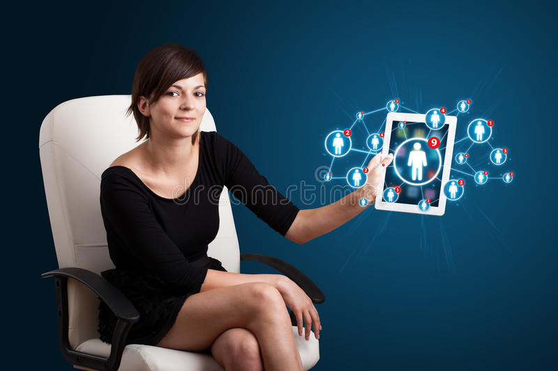 Young woman holding tablet with social network icons stock photos