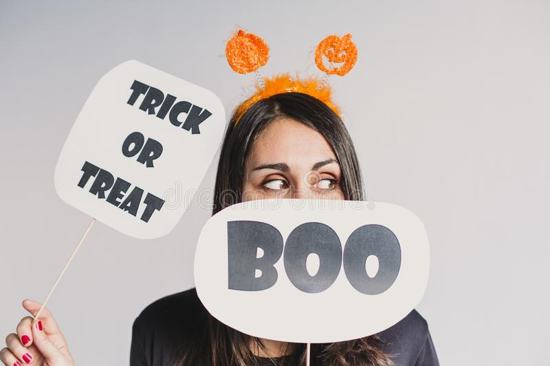 Young woman holding a trick or treat and a boo sign. Wearing a black and white skeleton costume. Halloween concept. Indoors. Lifestyle, holiday, pumpkin, fall stock images