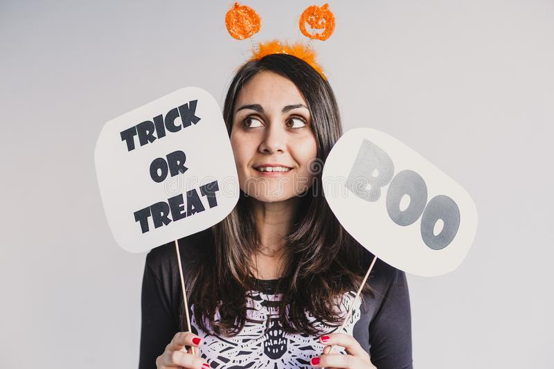 Young woman holding a trick or treat and a boo sign. Wearing a black and white skeleton costume. Halloween concept. Indoors. Lifestyle, holiday, pumpkin, fall stock photo