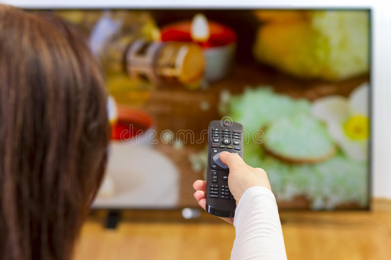 Young woman holding tv remote and surfing programs. Over the shoulder view of girl sitting on sofa holding tv remote and surfing programs on television. Focus on stock images
