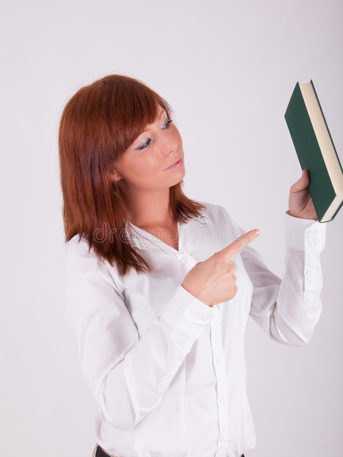 A young woman is holding up a book