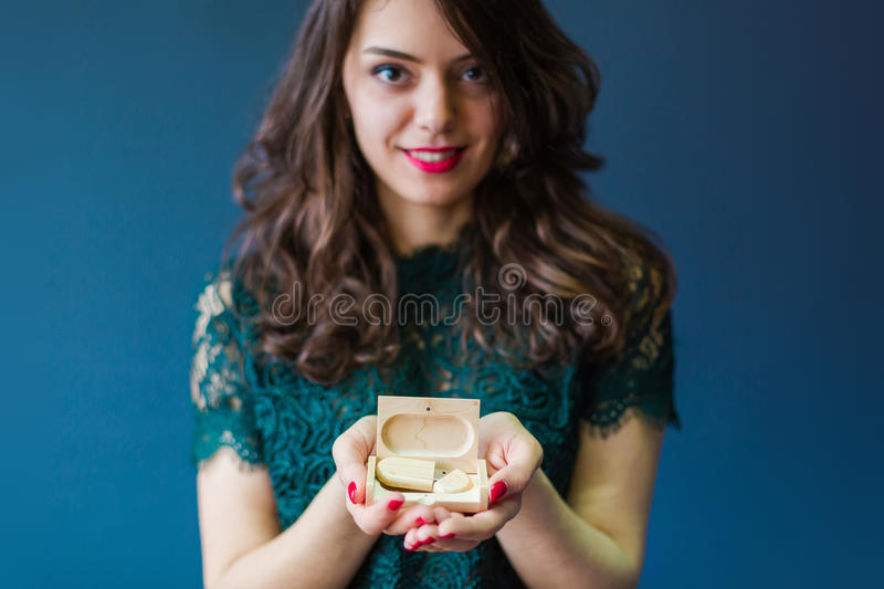 Young woman holding usb stick and case for it. Young woman holding wooden usb stick and case for it in hands, closeup stock photography