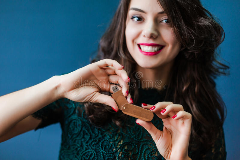 Young woman holding usb stick. Young smiling woman holding wooden usb stick in hands stock photography