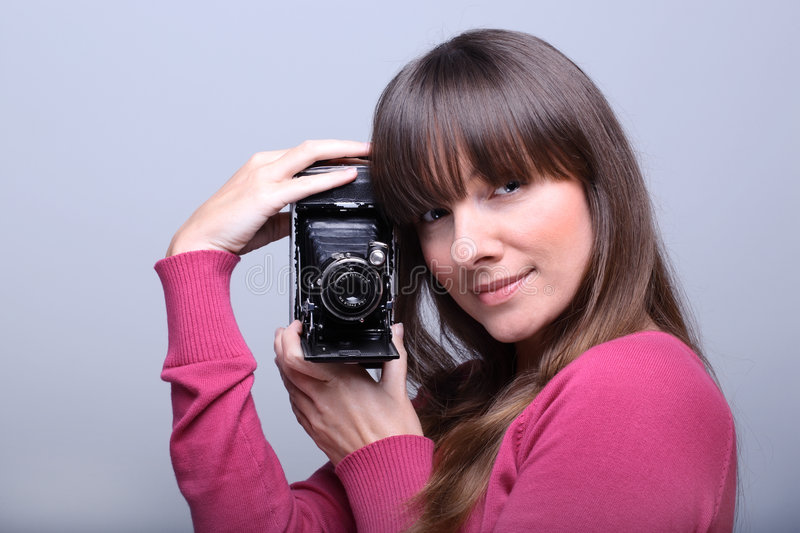 Young woman holding a vintage photo cam. Young beautiful woman holding a vintage photo camera royalty free stock photo