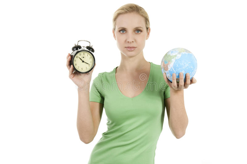Young woman holding a wake up alarma and the Earth. Concepts: time to wake up, time to protect the Earth royalty free stock photography
