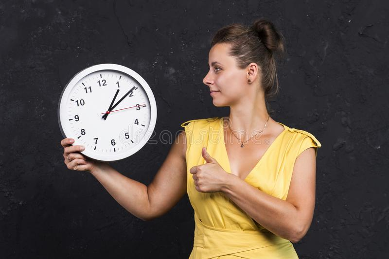 A young woman is holding a watch. Time concept. A girl with a clock in her hands. Keep track of time royalty free stock photo