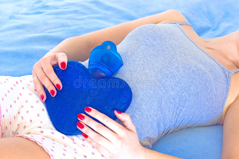 Abdominal pains. A young woman holding a water bottle on her stomach to alleviate stomach problems, photography stock images