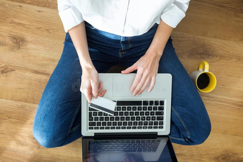 Young woman holding white credit card for shopping online with computer while sitting on the floor at home stock photography