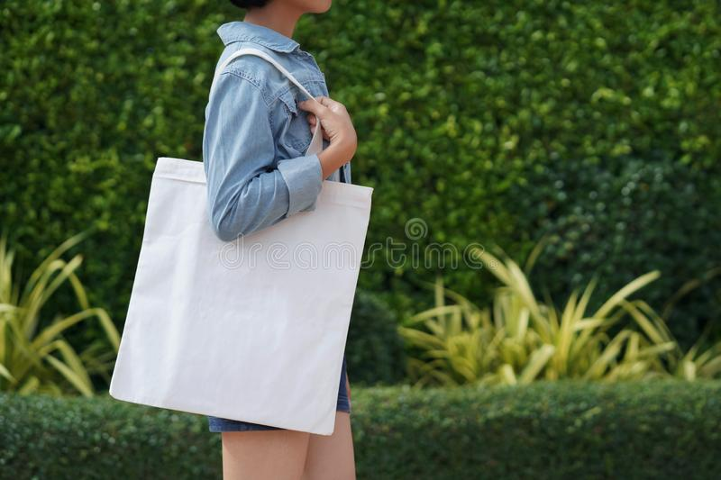 young woman holding white fabric bag walking in park stock photography