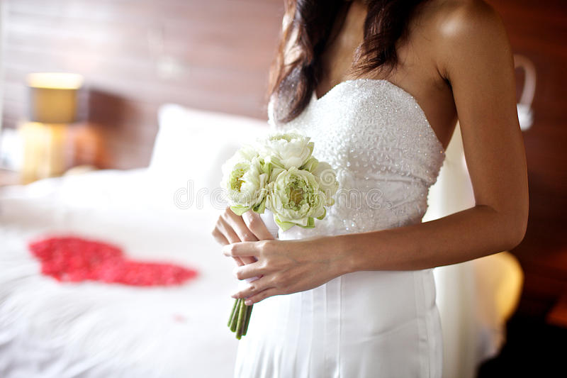 Young woman holding white lotus wedding bouquet. Withe red heart flower in background royalty free stock images