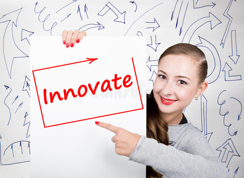 Young woman holding whiteboard with writing word: innovate. Technology, internet, business and marketing. Young woman holding whiteboard with writing word royalty free stock photos