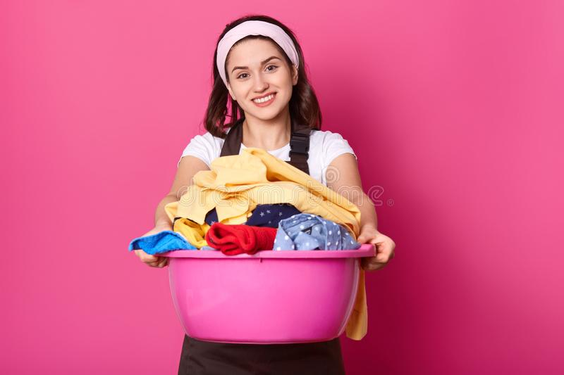 Young woman holds basin full of clean linen. Beautiful housewife looks happy after doing laundry. Smiling female works about house royalty free stock photo