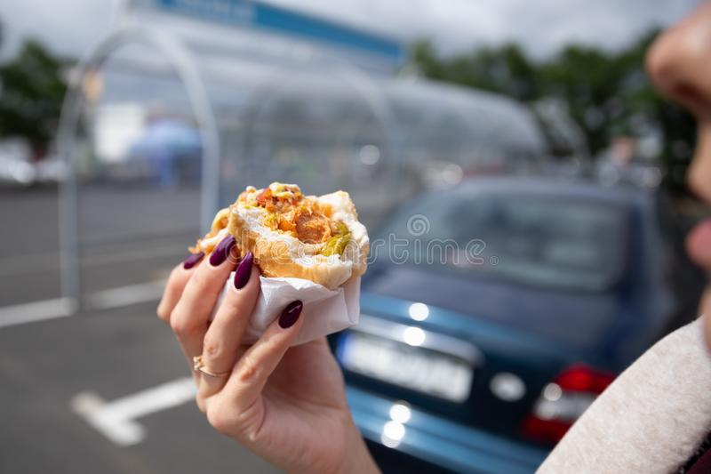 A young woman holds a bitten hot dog royalty free stock photo
