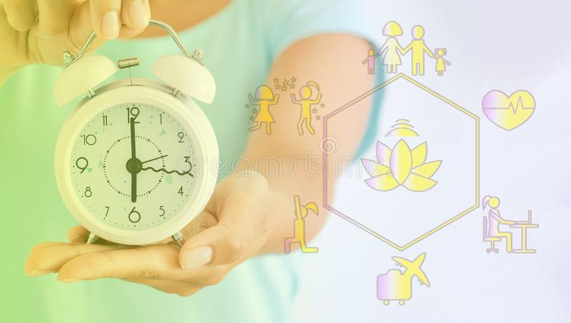 Young woman holds a clock, an alarm clock, and a diagram with the main goals in life, how to find a balance in life, a royalty free stock images