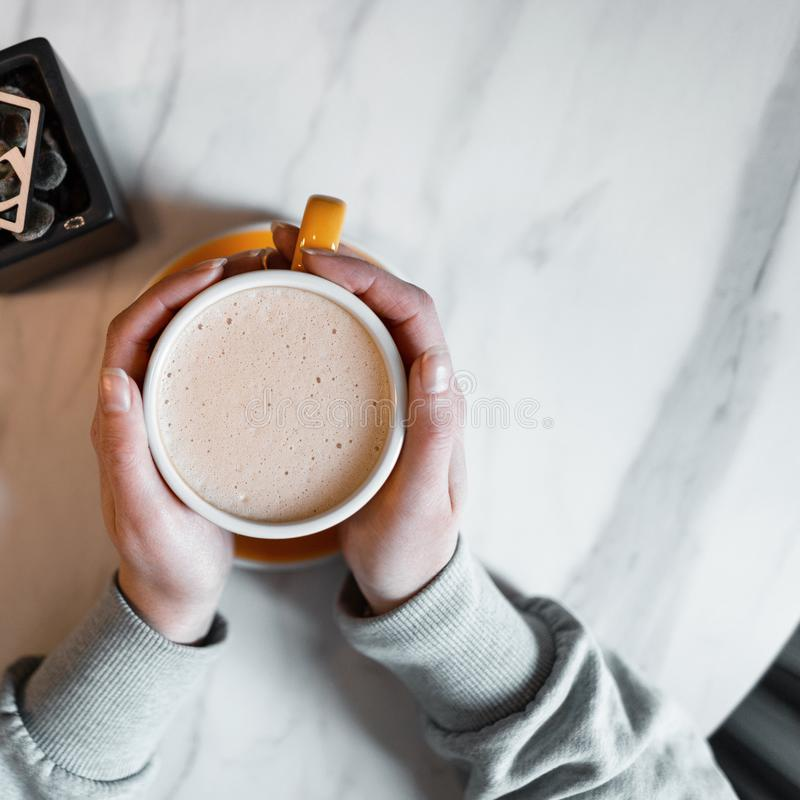 Young woman holds a cup of delicious hot americano with milk while sitting in an vintage coffee shop. Coffee gourmet. Good morning. View from above royalty free stock photo