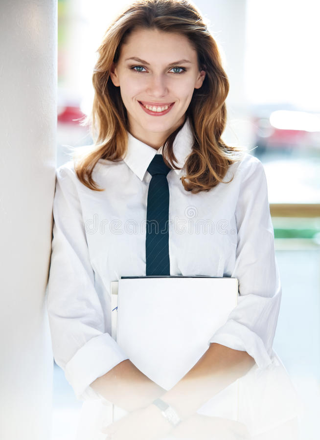 Young woman holds folders. Women in a white button down shirt with black tie royalty free stock photo