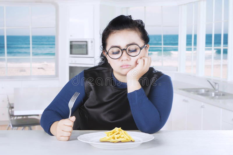 Young woman holds fork with french fries stock images
