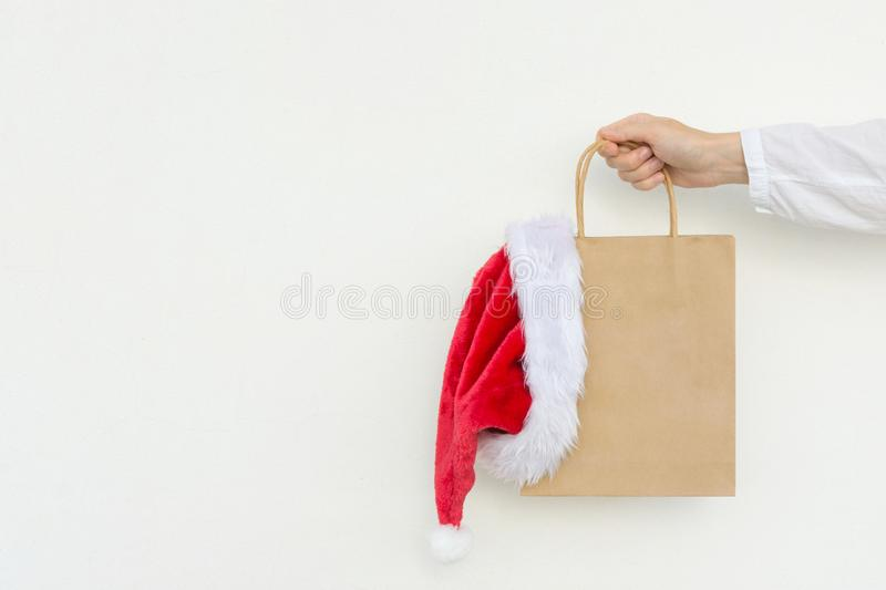 Young woman holds in hand empty blank mock up brown craft paper bag with hanging santa claus hat on white wall. Christmas royalty free stock photography
