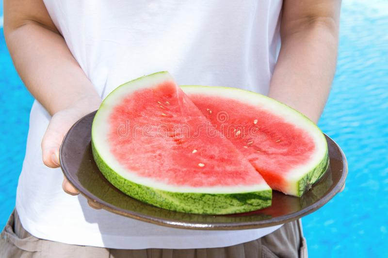 Young Woman Holds in Hands Plate with Juicy Watermelon Slices by Swimming Pool . Sunlight. Vacation Relaxation Summer royalty free stock image
