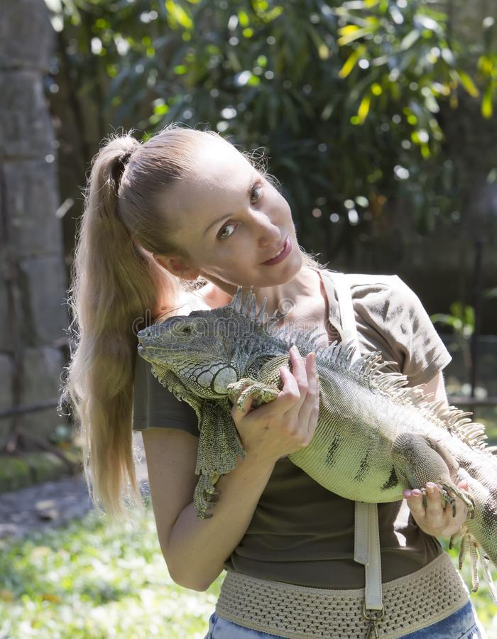 The young woman holds iguana on hands stock photography
