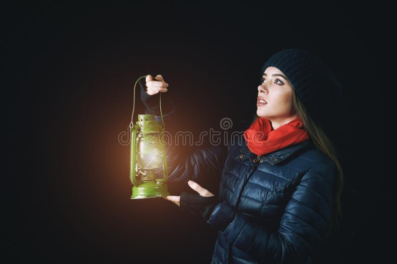 A young woman holds a kerosene lamp in the hands royalty free stock photos