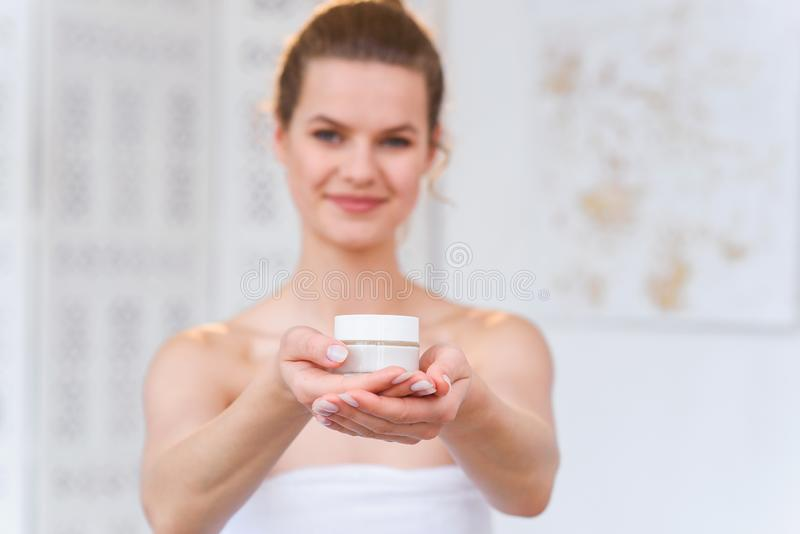 Woman holds a organic natural cream in her hand to moisturize her skin and wrinkle from impurities. Beauty, body care stock photography