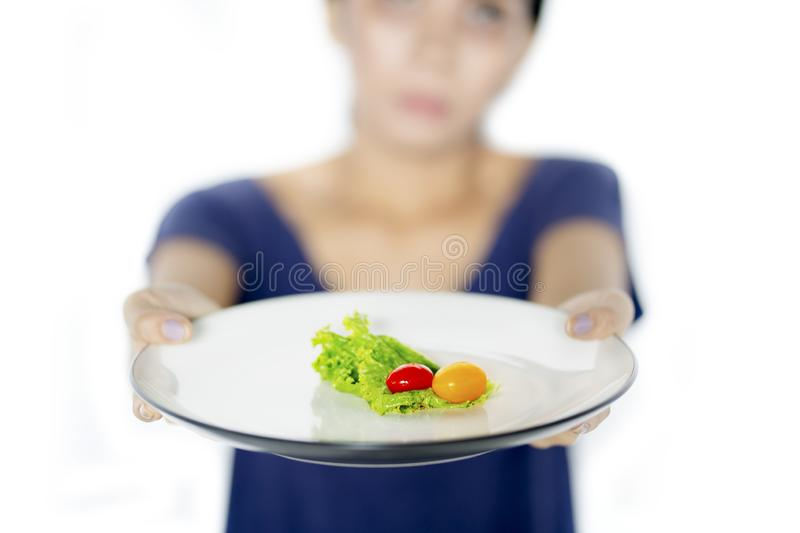 Young woman holds small portion salad on studio. Eating disorder concept. Young woman holding a plate of small portion salad, isolated on white background stock photo