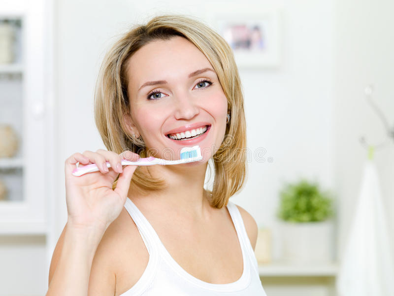 Young woman holds  toothbrush with a toothpaste