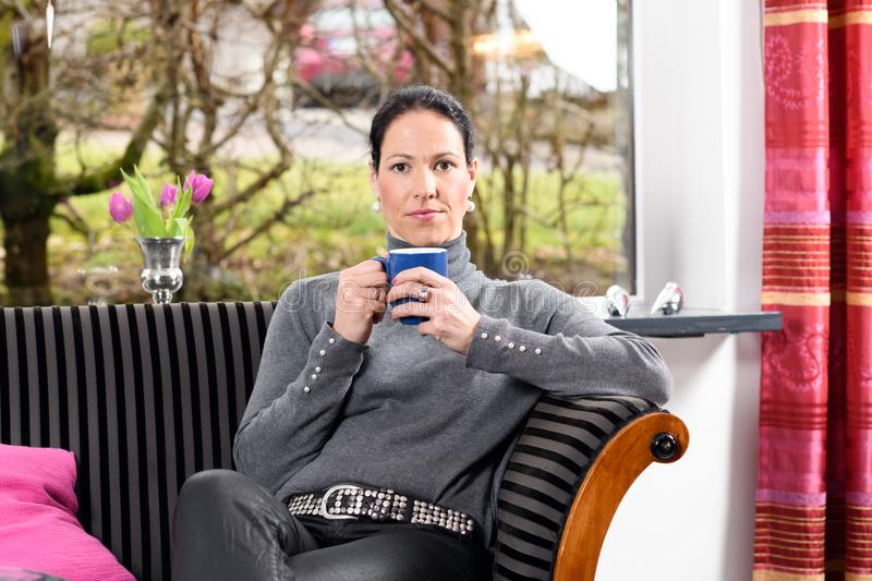 Young woman at home with cup of coffeee relaxing. Young dark haired woman at home with cup of coffeee relaxing royalty free stock photo