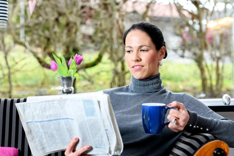 Young woman at home with cup of coffeee relaxing and reading n. Young dark haired woman at home with cup of coffeee relaxing and reading newspaper royalty free stock photo