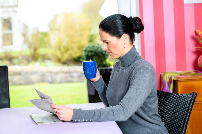 Young woman at home with cup of coffeee relaxing. Young dark haired woman at home with cup of coffeee reading newspaper royalty free stock image