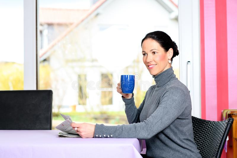 Young woman at home with cup of coffeee relaxing. Young dark haired woman at home with cup of coffeee reading newspaper stock images