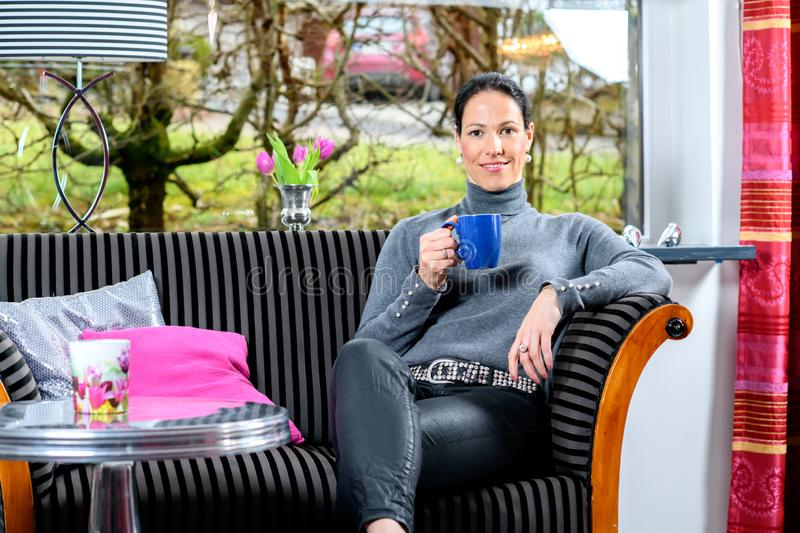 Young woman at home with cup of coffeee relaxing. Young dark haired woman at home with cup of coffeee relaxing royalty free stock photography