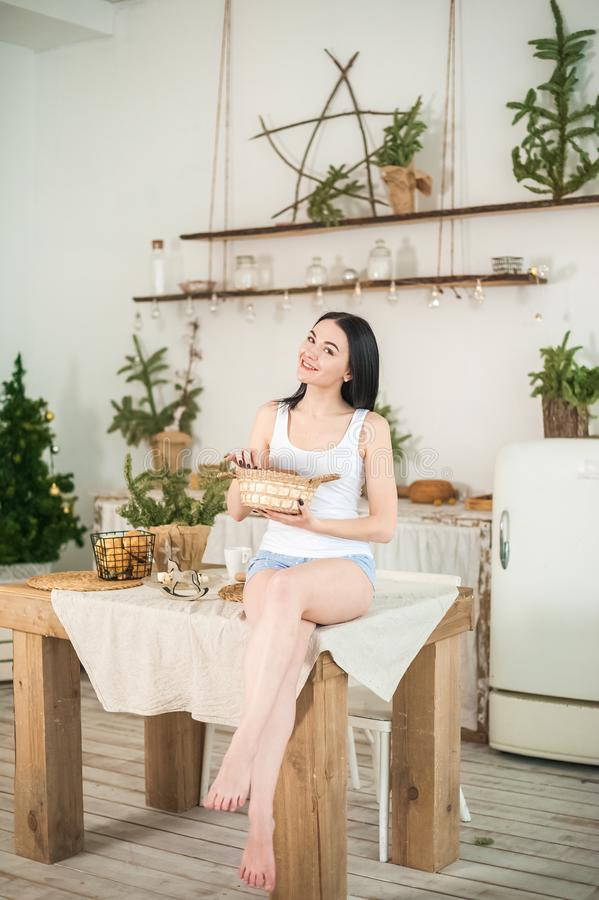 Young woman at home in the morning in the kitchen in light colors. The girl eats cookies, opens the refrigerator, prepares ginger. Cookies. Morning breakfast in royalty free stock photos